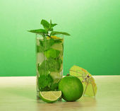 Mojito glass, an umbrella, a leaf of mint and a juicy lime on a table — Stock Photo