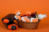 Shower gel, shampoo and big set of cosmetics, in a wattled basket, on an orange background — Stock Photo