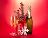 Champagne, branche de sapin avec des guirlandes, coffret cadeau, flocon de neige sur fond rouge — Photo