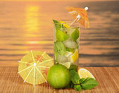 Mojito with umbrellas, a juicy lime, a lemon on a bamboo cloth against the sunset — Stock Photo