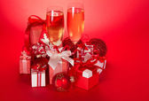 Two wine glasses with champagne, gift boxes with bows and tapes, Christmas spheres and serpentine on a red background — Stock Photo