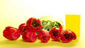 Bouquet of tulips with a green tape and a card for the letter on a yellow background — Stock Photo