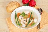 Tallrik med soppa, en sked, bröd och röda tulpaner på en beige servett — Stockfoto