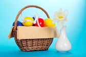 Easter eggs in a basket with a napkin and a vase with narcissus, on the blue — Stock Photo