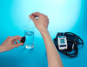 Hand with medical drops, a glass with water and a tonometer on a blue background — Stock Photo