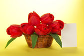 Bouquet of red tulips in a basket and a white card for the letter, on a yellow background — Stock Photo