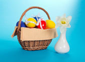 White narcissus in a ceramic vase and eggs in a wattled basket, on the blue — Stock Photo