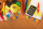 Blank exercise book sheets, a set for the letter and drawing, a calculator scissors and apple on a table — Stock Photo