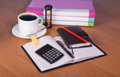 Notepad, organizer, folders for documents the calculator, hourglasses and a cup of coffee on a table — Stock Photo