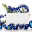 Fir-tree branch with tinsel, small gift boxes, a Christmas toy and a card isolated on white — Stock Photo