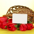 The red tulips which have dropped out of a basket, and white empty card for the letter, on a yellow background — Stock Photo #32300041