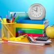 Pile of books, an exercise book, office supply, the calculator, an alarm clock and apple on a table — Stock Photo
