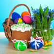 Festive easter food and vase with the flowers on a table, on a blue background — Stock Photo
