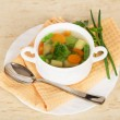 Cup with soup, a spoon, parsley and green onions, a napkin on the beige — Stock Photo