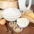 Cottage cheese, cheese,spices, butter, mixer and cake pan on a table — Stock Photo