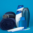 Towel, the razor, cosmetics, toothbrush and paste on a blue background — Stock Photo #32301951