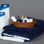 shampoo, gel, instellen in een gevlochten mand, een handdoek op een grijze achtergrond cosmetica — Stockfoto #32302167