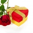 Bright red gift box in the form of heart with gold bow and rose isolated on white — Stock Photo