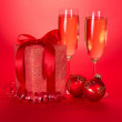 Christmas gifts, toys, serpentine and wine glasses with champagne on a red background — Stock Photo