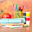Writing materials, paints and an apple, on a table — Stock Photo