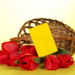 The red tulips which have dropped out of a basket, and empty card for the letter, on a yellow background — Stock Photo #32302569