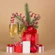 Christmas gifts, toys, tinsel, fir-tree branch, champagne and empty card, on a beige background — Stock Photo #32302927