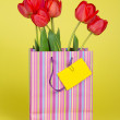Bouquet of tulips in a gift package and an empty card on a yellow background — Stock Photo #32302967