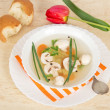 Plate with soup on a dish with a striped napkin, a spoon, bread and a red tulip — Stock Photo #32303013