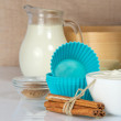 Cinnamon sticks, milk, sour cream and a cake pan, on a beige canvas — Stockfoto