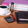 Stockfoto: Notepad, organizer, pencil and pen, folders for documents the calculator, hourglasses and a cup of coffee on a table
