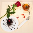 Chocolate cake, hot tea and red rose on a tablecloth decorated with hearts — Stock Photo