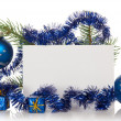 Fir-tree branch with tinsel, small gift boxes, two Christmas toy and a card isolated on white — Stock Photo