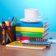 Stock Photo: Books, exercise books, office accessories in a support, a hourglass a cup of coffee on a table