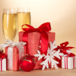 Two glasses with champagne, a set of gift boxes a snowflake and a Christmas toy on a beige background — Stock Photo #32304091