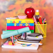A set of school accessories, a cake, apple and drink on a table — Stock Photo #32304451