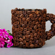 The cup made of grains of coffee, a branch of bright carnation on a grey background — Stockfoto