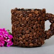 The cup made of grains of coffee, a branch of bright carnation on a grey background — Stock Photo