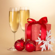 Wine glasses with champagne, christmas gift, snowflake and christmas toys on a beige background — Stock Photo