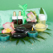 Stock Photo: Set for aromatherapy, candles and terry towel with bow, on green background