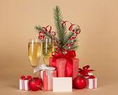 Champagne, fir-boomtak met klatergoud, geschenkdozen, speelgoed en lege kaart op een beige achtergrond — Stockfoto