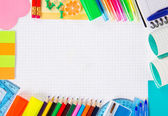 The exercise book leaf and a lot of office supply — Stock Photo