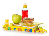 Set of school supplies, apple,sandwich on the striped napkin, bottle with compote — Stock Photo