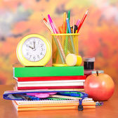 Books, alarm clock, a pencil-case with school accessories, paint and apple — Stockfoto