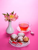 Cup with tea, a spoon and cupcakes on a dish, on the pink — Stock Photo