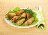 Pannenkoeken met zalm en salade, bestek op bamboe servet — Stockfoto
