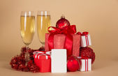 Christmas gifts, toys, tinsel, champagne and empty card, on a beige background — Stock Photo
