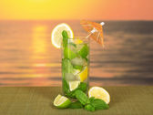 Cold drink with a lemon slice, spearmint, on a green bamboo cloth against the sunset — Stock Photo