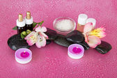 Aromatic oil, salt, candles, stones, flower, on a damp pink background — Stock Photo