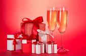 Två glas champagne, presentaskar med band och rosetter och kronblad av blommor på en röd bakgrund — Stockfoto