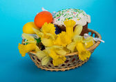 Easter cake, eggs and flowers in a basket, on a blue background — Stock Photo